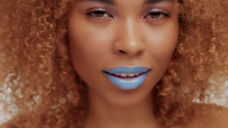 woman with bright blue lips shows tong Closeup video ideal skin texture