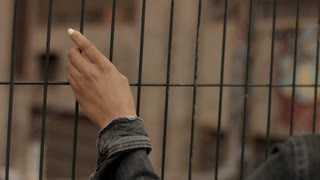 woman's hand touching a railing of iron barred fence