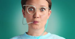 wondering woman drinks using drinking straw glasses with blue liquid