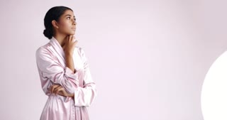 Young Middle Eastern model wearing light pink shiny dressing gown with her hair up in a cosmetology clinic