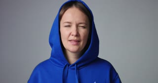 Young woman in large unlabeled bright blue hoodie screams and acts scared and angry isolated on white