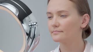 young woman sad about her skin looking at beauty mirror
