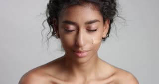 Young woman with beautiful olive skin applying liquid foundation or BB cream to her cheeks isolated on white