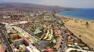 Breathtaking aerial view of the Gran Canaria Maspalomas dunes by the city and the ocean. View from above.