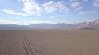Endless road t horizon through the Death valley. View from above. Sunset in a desert.