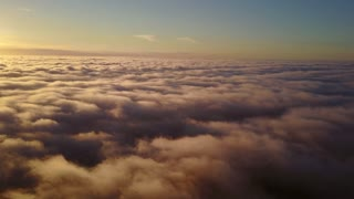 Rising through the clouds into the sky and sunset. Flying above the clouds during sunset