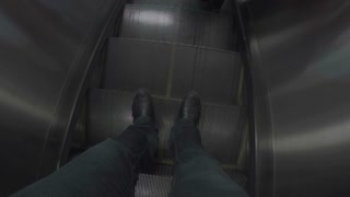 POV of feet moving down and getting off escalator.