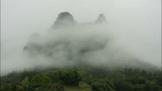 Timelapse of clouds over giant green mountain in China.