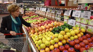 Adult older woman browses and buys fruit.