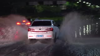 Car fords torrential rain flooded highway.Chinese water covered road with vehicles. Cars slowly traversing hazardous road in typhoon conditions.