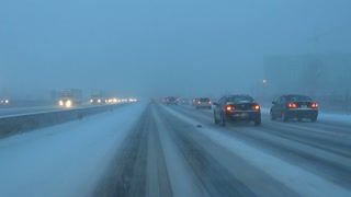 Driving down snow covered highway at rush hour in Canada. Speeding down a hazardous snowy freeway avoiding a crash. Wipers against snowfall on the dangerous road. High speed on slippery road.