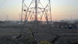Drone flying up high voltage electricity tower and power lines at sunset.Power transmission pylons nearby city at disk. From base to top of girders on high voltage wires tower.