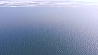 Melting frozen ice shelf on water.Drone shot flying over water to edge of ice shelf that has partially melted. Global warming and climate change effects on edge of the ice.