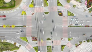Motion blur fast traffic intersection from above. Modern green traffic crossing from aerial drone in Jiashan, China. Cars, trucks and scooters crossing a busy traffic light on a beautiful summer day.