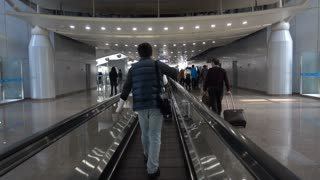 Moving walkway at busy airport in Asia. Travelator, people mover at Pudong Airport in Shanghai. Horizontal escalator device moves passengers and luggage along the hallway.