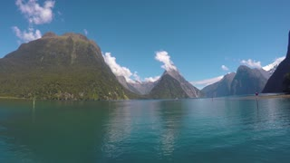 Sailing through beautiful mountains and water fiord in New Zealand. Boat tour in South Island Milford sound. World heritage site Piopiotahi in Fiordland National Park.