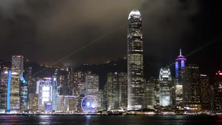 Time lapse of Hong Kong Island skyline at night. 	Timelapse of HK financial district and ferris wheel near Central in downtown at nighttime. Harbor with boats and ferries lit up.