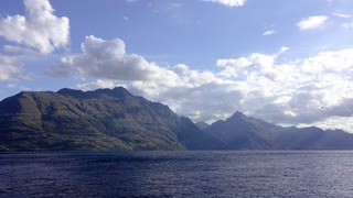 Time-lapse of mountains by the sea in Queenstown New Zealand. Moving clouds on blue sky and massive hills and water in picturesque timelapse.