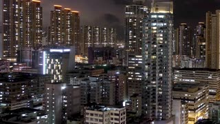 Timelapse at night of Hong Kong residential apartments. Chinese crowded city with lights turning on and off at midnight. Fast paced modern asian night-scape time lapse in urban metropolis.