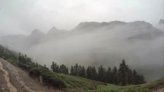 Timelapse of clouds over mountain dirt road in China. Ancient mountain cloudy time lapse drifting on Chinese forested hills on overcast rainy day. Cloudy mist billows across forest covered peaks.