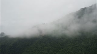 Timelapse of clouds over mountain edge in China.Ancient mountain cloudy time lapse drifting on Chinese forested hills on overcast rainy day. Cloudy mist billows across forest covered peaks.