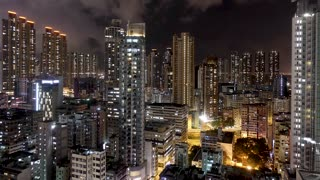 Wide timelapse at night of Hong Kong residential apartments. Chinese crowded city with lights turning on and off at midnight. Fast paced modern asian night-scape time lapse in urban metropolis.