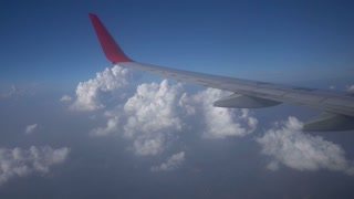 Wing of plane passing over white fluffy clouds.