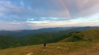 a man in the mountains makes a photo of a rainbow