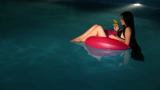 attractive girl in pool with cocktail