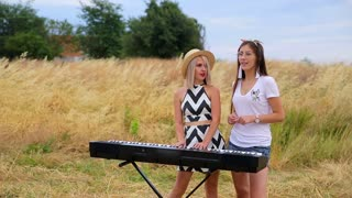 blonde and brunette play the synthesizer and sing in the field