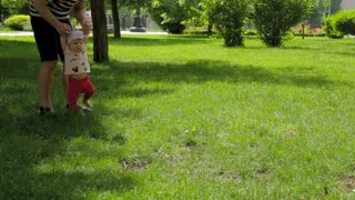 Dad helps his daughter take the first step in the park on the grass