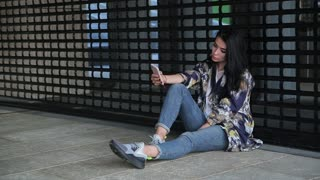 sad girl with a phone sits at the cage