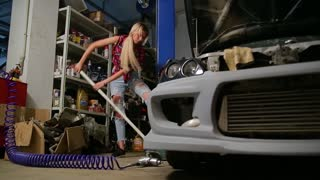 sexy blonde girl jacks up a car in the garage