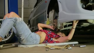 sexy blonde is lying under the car in the garage and repairing it
