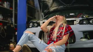 tired sexy blonde smokes at the car in the garage