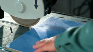 Worker cuts ceramic tiles on a tile cutting machine