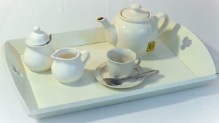 Pour tea into a cup on a tray 4K
