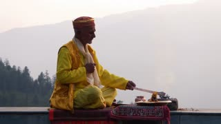 A Hindu old man in yellow national costume offering special spiritual prayer to god in the foothills of the Himalayas, Kullu Valley, India