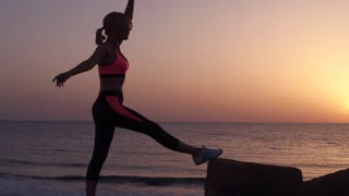 a young woman is engaged in gymnastics at sea at sunset silhouette