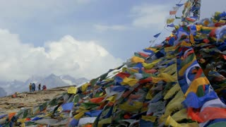 Buddhist colorful prayer flags blow by the wind in the mountains in Himalayas, India.