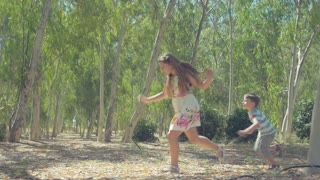 Children play catch-up in a sunny forest among the trees