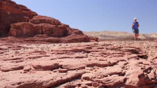 Climber in equipping exploring new places. Red stone desert in the foreground