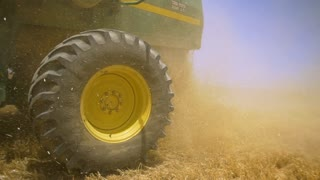 Combine work during the harvest season. The camera turns from the wheel to the general plan of harvesting machines