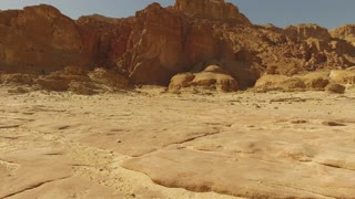 Discovery of new places. The traveler in the desert.Girl with a backpack walking along the stone red desert. Steady shot