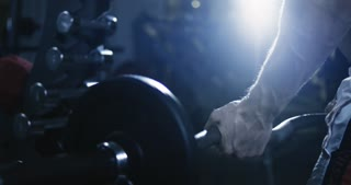 Handsome man lifting heavy free weights at the gym