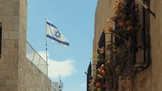 Israel national flag against the Western Wall in Jerusalem, Israel.