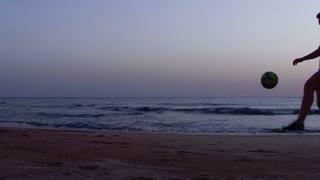 Man Juggling Soccer Ball Close Up on Seashore at Sunset