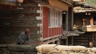 MANALI, INDIA - 28 SEPT 2016: An unidentified old Indian man hides from the heat in the shade of the stone house in the Indian village, Himachal Pradesh, Kullu Valley