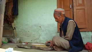 MANALI, INDIA - 28 SEPT 2016: An unidentified old Indian man sits and rubs grain by stone in front of his house in the Indian village, Himachal Pradesh, Kullu Valley