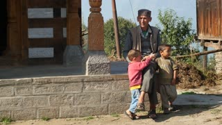 MANALI, INDIA - 28 SEPT 2016: Indian father and sons seat outside the house in Indian village, Himachal Pradesh, Kullu Valley